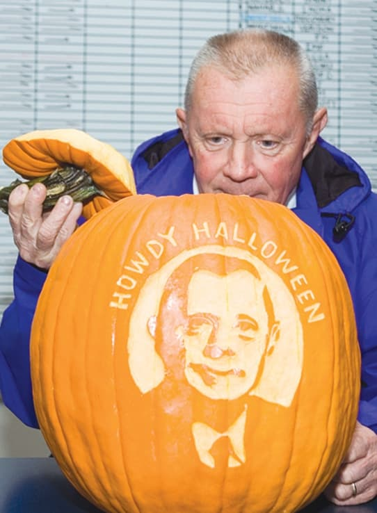 Russell inspects a pumpkin with his likeness